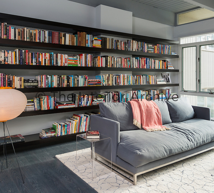 A contemporary home library room with wall to wall book shelves. A comfortable grey upholstered sofa is set on a patterned rug on the grey cerused oak floor.