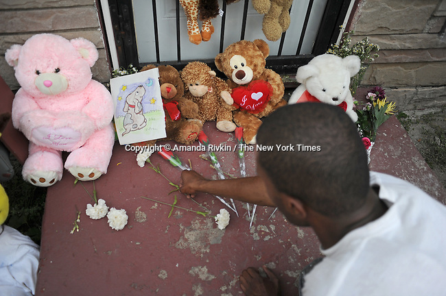 A neighbor of Michael Jackson's boyhood home leaves a flower on the stoop shortly after he passed away at a Los Angeles hospital outside the home at 2300 Jackson Street in Gary, Indiana on June 25, 2009.