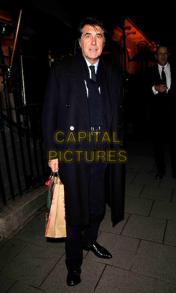 BRYAN FERRY.The Tommy Hilfiger special dinner, Annabel's bar & club, London, England..April 14th, 2008.full length black coat scarf goody bag .CAP/CAN.©Can Nguyen/Capital Pictures.