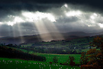 Rays of sunlight shining through clouds onto green fields