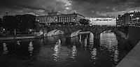 Riksdagshuset och Riksdagsbron i skymning en sen kväll vid Stockholms ström i svartvitt.