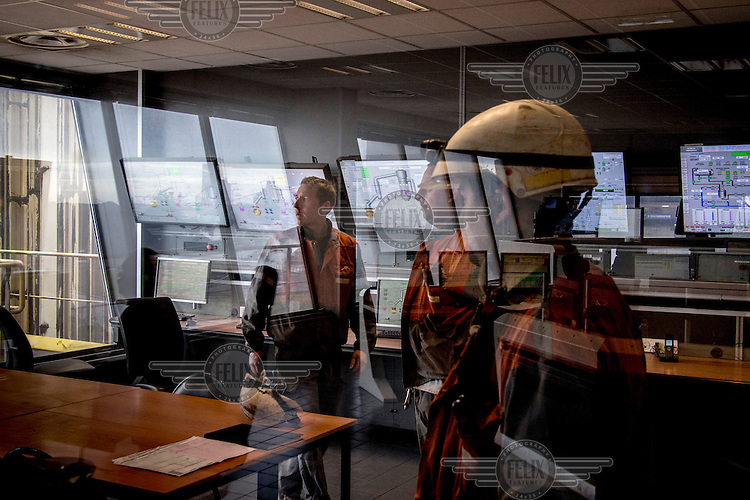 Workers check information from screens in a control room at the Arcelormittal steelworks.