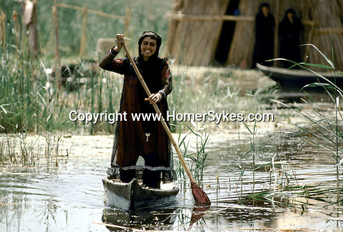 Marsh Arabs. Southern Iraq. Circa 1985. Marsh Arab woman standing in boat rowing between traaditional reed island homes. MARSH ARAB WOMAN, DRESSED IN TRADITIONAL CLOTHING, STANDING UP IN WOODEN CANOE PADDLING IT FORWARD WITH OAR, Haur al Mamar or Haur al-Hamar marsh collectively known now as Hammar marshes Irag 1984