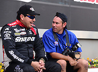 Sept. 14, 2012; Concord, NC, USA: NHRA funny car driver Cruz Pedregon (left) talks with National Dragster photographer Marc Gewertz during qualifying for the O'Reilly Auto Parts Nationals at zMax Dragway. Mandatory Credit: Mark J. Rebilas-