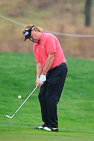 Miguel Angel Jimenez (ESP) chips onto the 1st green during Thursday's Round 1 of the 2014 BMW Masters held at Lake Malaren, Shanghai, China 30th October 2014.<br /> Picture: Eoin Clarke www.golffile.ie