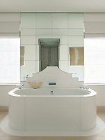 The stylish bathroom features a deep, free-standing bath in the centre of the room.