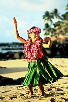 Young Hawaiian girl  (age 7) dancing a modern (auana) hula on the beach in a ti leaf skirt with orchid leis
