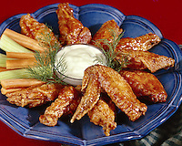 "Hot Chicken wings ""Buffalo Wings"" with blue cheese dressing and vegetable sticks on the side"