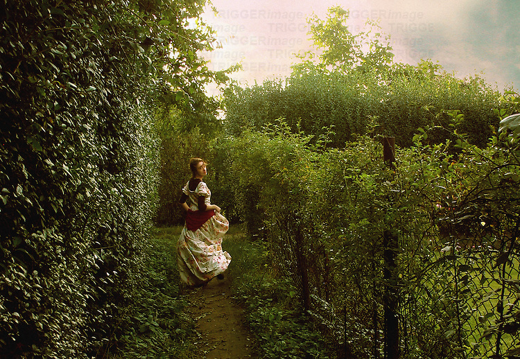 A woman in a white dress with a red motif, running along a path in a garden, with the sun setting behind the trees.