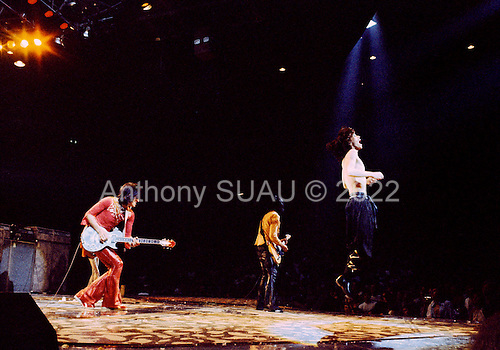Chicago, Illinois<br /> July 23, 1975<br /> USA<br /> <br /> Lead singer Mick Jagger, with guitarists Keith Richards (center) and Ronnie Wood (L) of the Rolling Stones performs live at Chicago Stadium during the band's &quot;Rolling Stones Tour of the Americas '75&quot;.<br /> <br /> This was the Stones first tour with new guitarist Ronnie Wood, after Mick Taylor left the band. The Stones, with their usual act freshly aided by theatrical stage props  including a giant inflatable phallus (nicknamed 'Tired Grandfather' by the band, since it sometimes malfunctioned) and, at the Chicago shows, an unfolding lotus flower-shaped stage that Charlie Watts had conceived.<br /> <br /> The band was composed of  Mick Jagger - vocals, guitar, harmonica, Keith Richards - guitar, vocals, Bill Wyman - bass guitar, and Charlie Watts - drums, percussion. <br /> <br /> Additional musicians included: Ronnie Wood - guitar, backing vocals, Ian Stewart - piano, Billy Preston - keyboards, vocals and Ollie Brown - percussion.