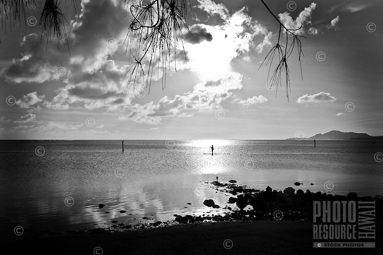 Hawaiian man on a standup paddleboard at Maunalua Bay Beach Park, Hawai'i Kai, O'ahu.