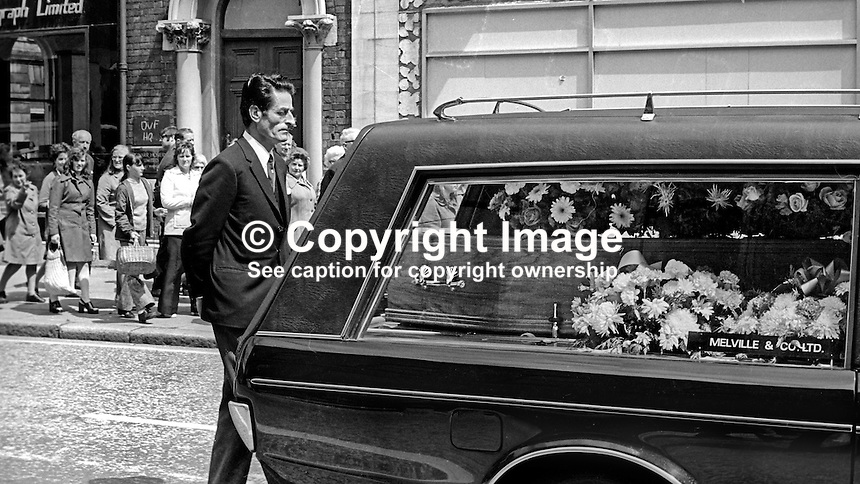 Funeral of N Ireland comedian James Young, 9th July 1974. His longterm partner and stage colleague, Jack Hudson, follows the hearse as it passes along Bedford Street where they both enjoyed spectacular success in the Group Theatre. 197407090382d<br />