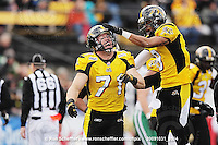 October 31, 2009; Hamilton, ON, CAN;  Hamilton Tiger-Cats defensive end Garrett McIntyre (71) celebrates recovering a Saskatchewan Roughriders fumble with defensive back Geoff Tisdale (9). CFL football: Saskatchewan Roughriders vs. Hamilton Tiger-Cats at Ivor Wynne Stadium. The Tiger-Cats defeated the Roughriders 24-6. Mandatory Credit: Ron Scheffler. Copyright (c) 2009 Ron Scheffler.