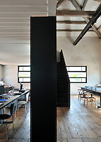 A functional, light industrial style space separated by a solid partition wall. The room has exposed roof beams and a wood floor. The room is divided into an office and meeting areas.