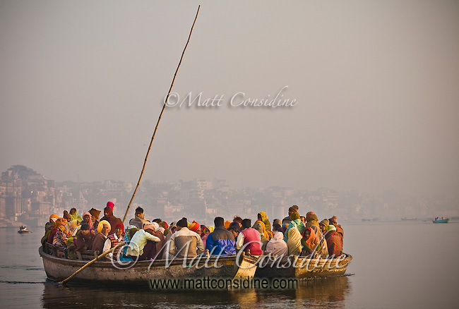 Boats packed with early morning pilgrims make their way through the mist and smoke along the Ganges.<br /> (Photo by Matt Considine - Images of Asia Collection)