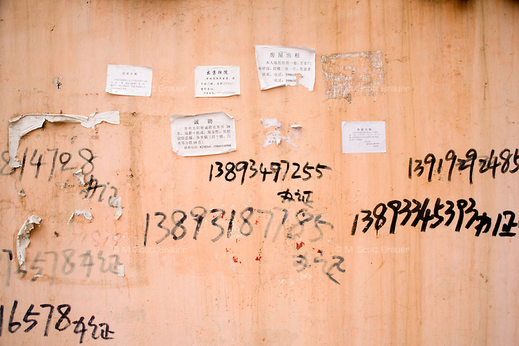 Day laborers' phone numbers are painted on a wall in Pingliang, Gansu, China.