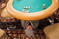 "Professional poker player Phil Laak, known as ""The Unabomber"" because he always wears a hooded sweatshirt, sleeps under a poker table during a break in the action  at the 36th annual World Series of Poker at the Rio on Thursday July 7, 2005 in Las Vegas, Nevada. Thursday marked the start of the no-limit Texas hold'em main event. Approximately 5,600 players are competing for a chance to win the first-place prize of roughly $7.5 million. (Photo by Landon Nordeman/ Getty Images)"
