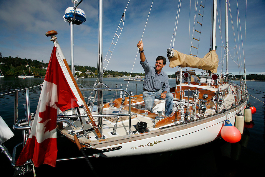 """Glenn Wakefield with his boat """"Kim Chow"""" on the docks at the Royal Victoria Yacht Club in Victoria, British Columbia. Wakefield plans to circumnavigate the world solo and non-stop on his sailboat. Photo assignment for Canadian Press (CP) news wire service."""