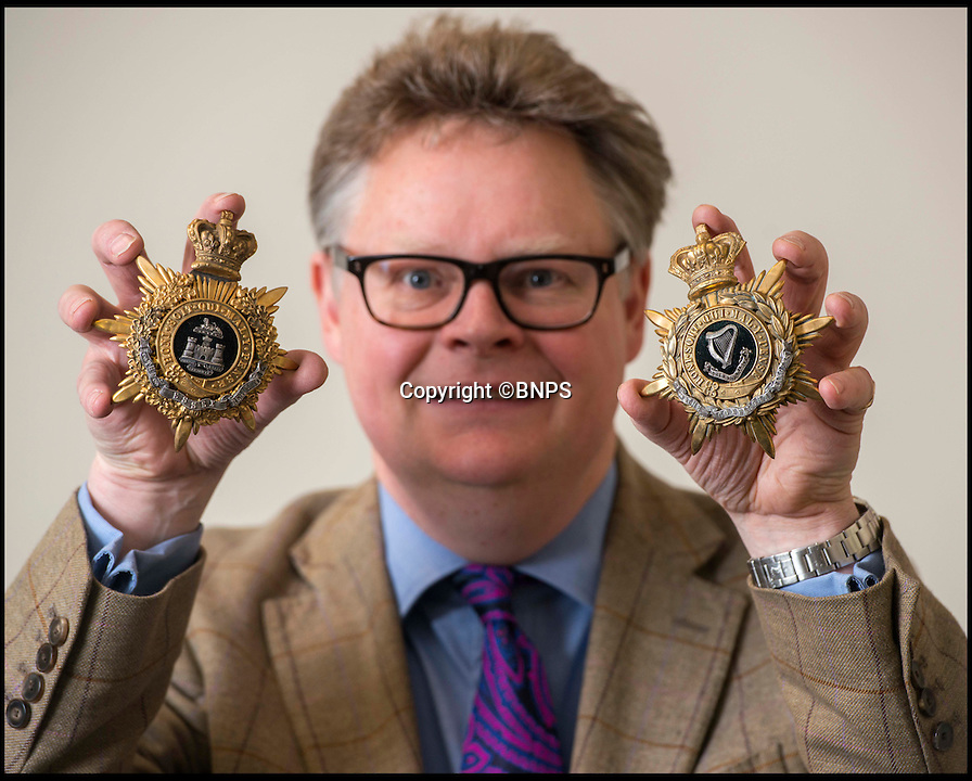 BNPS.co.uk (01202 558833)<br /> Pic: TomWren/BNPS<br /> <br /> Auctioneer Richard Bromell with two of the badges.<br /> <br /> A stunning collection of military badges amassed by one man has been unearthed to remember the lost regiments of the British Army.<br /> <br /> More than 800 brass badges recovered from old pith helmets, peaked caps and military tunics were amassed by the late collector over a lifetime.<br /> <br /> Many of the insignia date back to the Victorian era and represent regiments which no longer exist or which have been amalgamated, having either been decimated in the First World War or wiped out by government cuts.<br /> <br /> The collection is being sold by Charterhouse Auctioneers of Dorset.