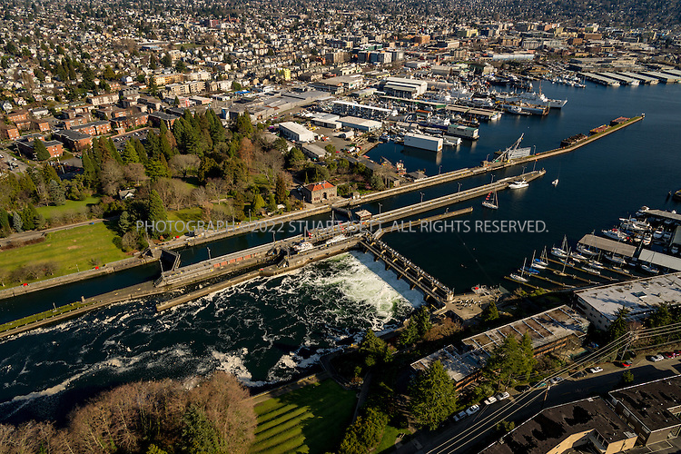February 8th, 2016 &mdash; Puget Sound, Seattle, Washington, USA<br /> <br /> Ballard Locks in Seattle, Washington. <br /> <br /> The Hiram M. Chittenden Locks, or Ballard Locks, is a complex of locks at the west end of Salmon Bay, in Seattle, Washington's Lake Washington Ship Canal, between the neighborhoods of Ballard to the north and Magnolia to the south.<br /> <br /> The Ballard Locks carry more boat traffic than any other lock in the US, and the Locks, along with the fish ladder and the surrounding Carl S. English, Jr., Botanical Gardens attract more than one million visitors annually, making it one of Seattle's top tourist attractions.The construction of the locks profoundly reshaped the topography of Seattle and the surrounding area, lowering the water level of Lake Washington and Lake Union by 8.8 feet (2.7&nbsp;m), adding miles of new waterfront land, reversing the flow of rivers, and leaving piers in the eastern half of Salmon Bay high and dry. The Locks are listed on the National Register of Historic Places and the American Society of Civil Engineers Historic Civil Engineering Landmarks.<br /> <br /> Photograph by Stuart Isett<br /> &copy;2015 Stuart Isett. All rights reserved.