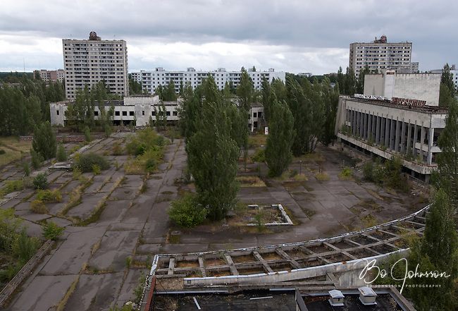 View over the central square from the deserted Hotel Polisye (Polissia?) in Pripyat. The central market and residential houses are across the square, and the Palace of Culture &quot;Energetik&quot; to the right.<br /> Pripyat was built 1970 as a modern city for personnel at the Chernobyl Nuclear Power Plant a couple of kilometers south. After the nuclear disaster at reactor 4 on April 26 1986, the town's 48.000 inhabitants was evacuated to other parts of the country. Pripiat is today a radioactive ghost town. The whole area is contamined with nuclear material, the half-life of plutonium-239 is more than 24.000 years.<br /> Pripyat, Ukraine.<br /> August 2008.
