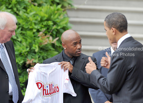 "Washington, D.C. - May 15, 2009 -- United States President Barack Obama, right, gives a ""thumbs-up"" to shortstop Jimmy Rollins, center, who is presenting a jersey to the President as the 2008 Baseball World Champion Philadelphia Phillies were welcomed to the White House in Washington, D.C. on Friday, May 15, 2009.  Phillies' manager Charlie Manuel looks on from left..Credit: Ron Sachs / Pool via CNP"