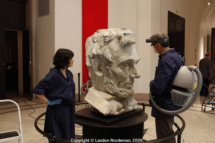 "NEW YORK - SEP 24: Alan Balicki, the Chief Conservator, and Elizabeth Fiorentino, the Registrar, surface clean the Lincoln Head Sculpture at the New-York Historical Society in New York on Thursday, September 24, 2009.  The bust of Lincoln will welcome visitors to the major new exhibition ""Lincoln and New York,"" at the New- York Historical Society. The plaster bust of Abraham Lincoln was made in 1922 by artist Daniel Chester French as a full-scale maquette for his Lincoln Memorial sculpture in Washington, DC. Measuring 43 ¾ inches in height, the maquette is being installed on a low pedestal, to give visitors a startling eye-level view of the familiar head, which in the Memorial looms far above them. Christopher Alzapiedi is the exhibitions tech, who is standing on the Genie, working on the lighting for the bust. (Photo by Landon Nordeman)"