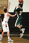James Sandoval, with Manogue, passes over Douglas defender Connor Hughes during a boys basketball game between Bishop Manogue and Douglas High in Minden, Nev., on Thursday, Dec. 22, 2011..Photo by Cathleen Allison