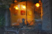 USA, Oregon, Sitting inside cafe viewed through rainy window.