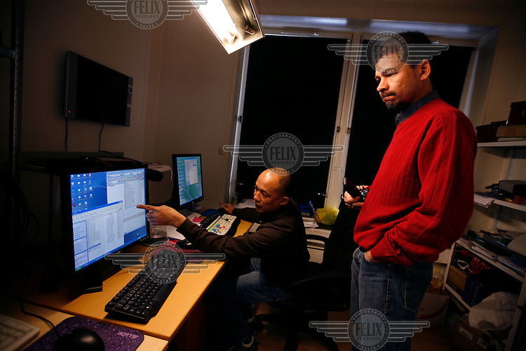 Technician Nay Zaw Naing working with executive editor Aye Chan Naing (red sweater). Democratic Voice of Burma is radio and TV station run by exiled Burmese. Opposing the government, the DVB has been transmitting, from the Norwegian capitol Oslo, into Burma since 1992.