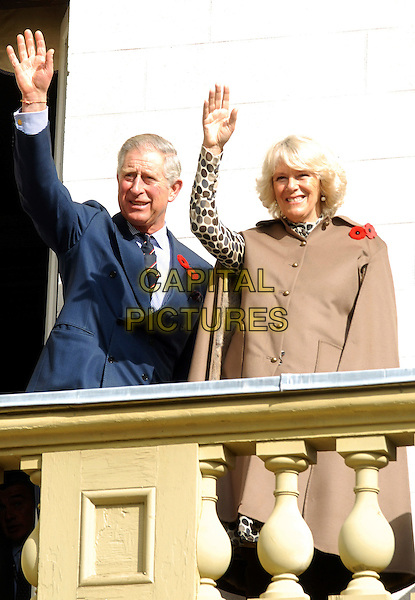 PRINCE CHARLES OF WALES & CAMILLA, DUCHESS OF CORNWALL.British Royals visit Dundurn Castle, the ancestral home of the Duchess of Cornwall, Hamilton, Ontario, Canada, .5th November 2009..half length hrh the married husband wife couple Parker Bowles royal brown cape coat poppy hand waving blue suit tie .CAP/ADM/BPC.©Brent Perniac/Admedia/Capital Pictures