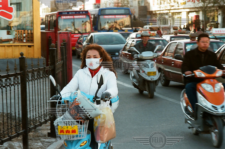 A woman, wearing a surgical mask, rides a scooter along a road busy with traffic in Datong.