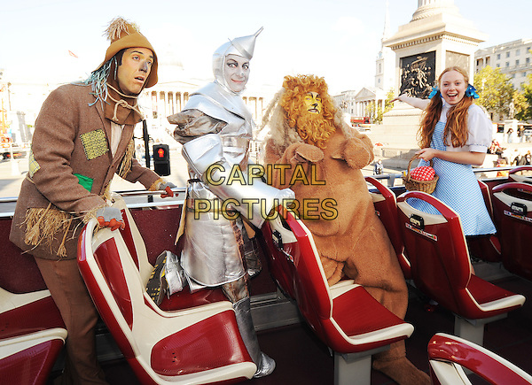 WIZARD OF OZ - Dorothy Gale, her faithful dog, Toto, the Cowardly Lion, the Tin Man and the Scarecrow .Wizard of Oz characters hit London streets to celebrate the 70th Anniversary release of the ultimate Sing-Along edition DVD & Blu-Ray..November 2nd, 2009.full length costume silver fur blue dress mouth open top deck bus tour trafalgar square  .CAP/PLF.Supplied by Capital Pictures.