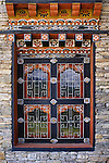 An ornate and beautifully decorated painted window in Chimi Lhakhang Temple reflecting the mountain landscape of Wangdue, Bhutan. The temple is dedicated to Lama Drukpa Kuenley (The Divine Madman).