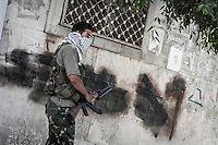 An opposition fighter holds his kalashnikov as he prepares to enter into the Holok industrial neighborhood which is under heavy sheling by Syrian helicopter and aircraft in Aleppo City.
