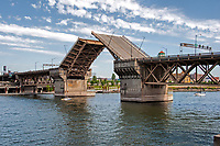 The Burnside Drawbridge raises to let sail boats by on the Willamette River waterfront in Portland, Oregon.