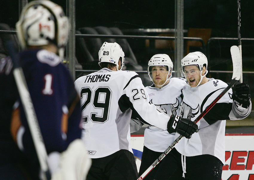 San Antonio Rampage players David Marshall, right, Tyson Strachan, middle, and Bill Thomas celebrate a goal on Oklahoma City Barons goaltender David LeNeveu, left, during the second period of an AHL hockey game, Saturday, Dec. 3, 2011, in San Antonio. (Darren Abate/pressphotointl.com)