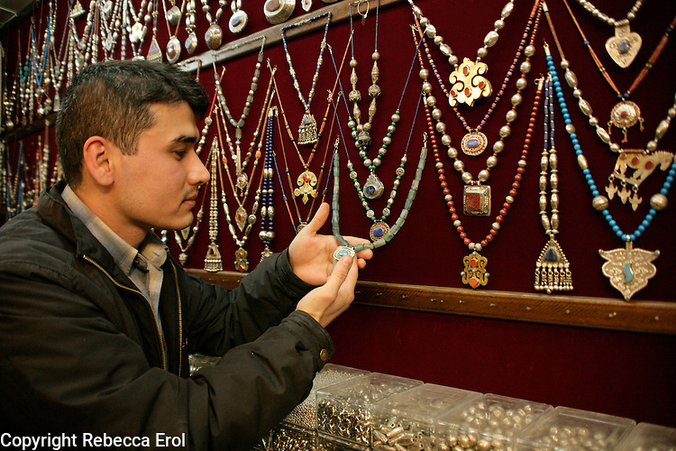 Turkoman salesman from Afghanistan showing traditional jewellery for sale in the Grand Bazaar, Istanbul, Turkey