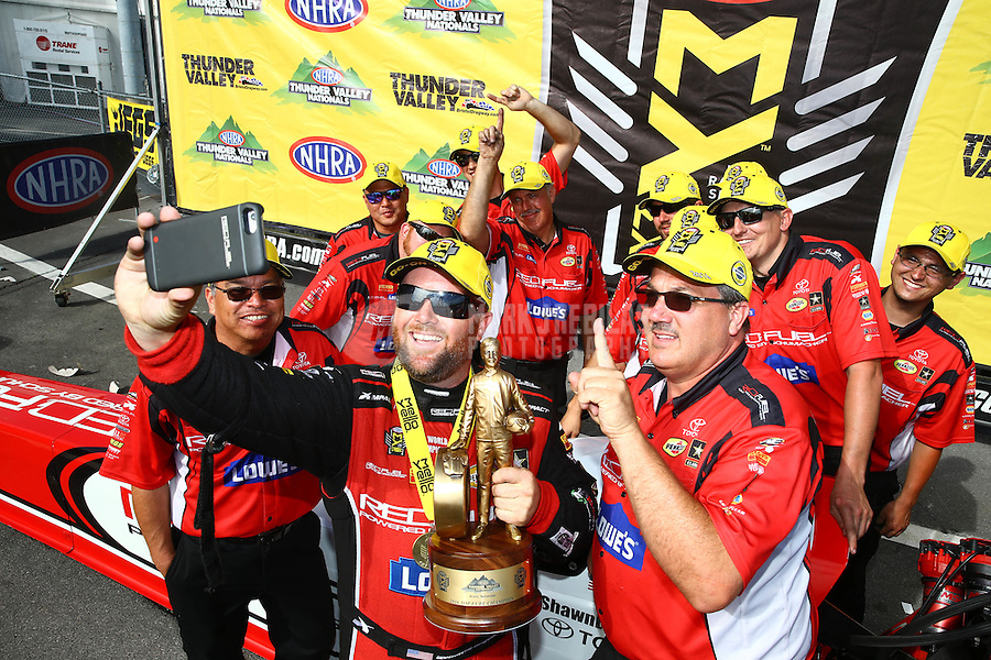 Jun 19, 2016; Bristol, TN, USA; NHRA top fuel driver Shawn Langdon (center) takes a selfie as he celebrates with crew after winning the Thunder Valley Nationals at Bristol Dragway. Mandatory Credit: Mark J. Rebilas-USA TODAY Sports