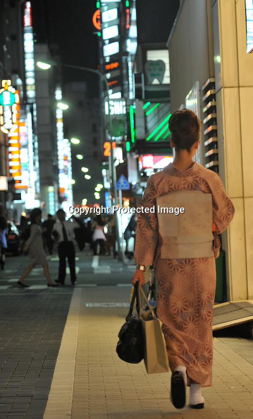 High-class hostesses, dressed in traditional Kimono make their way along a bar street lined with small exclusive clubs in the up-market  Ginza area of Central Tokyo, 17th September, 2008.<br />
