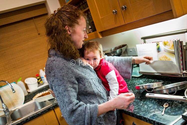 A woman reads a recipe while cooking and breastfeeds her 20 month old toddler at the same time.  The toddler is sitting on the kitchen work top.<br /> <br /> 07/02/2013<br /> Hampshire, England, UK