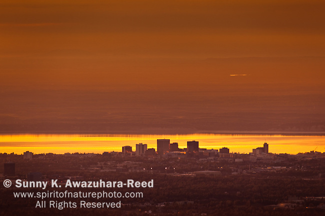 View of the Anchorage skyline with low clouds at sunset with Cook Inlet in the background, Southcentral Alaska, Summer.