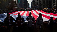 NEW YORK, USA - November 11: People hold a US flag as they attend the 100 Veterans Day parade on November 11, 2019 in New York, USA. President Donald Trump, the first sitting U.S. president attended New York's parade, where he offered a tribute to veterans ahead of the 100th annual parade  (Photo by Eduardo MunozAlvarez/VIEWpress)
