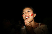 CHINA. Beijing. A young Chinese woman smiles whilst watching the opening ceremony of the Beijing Summer Olympics. 2008