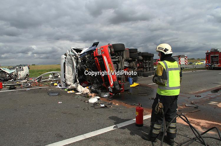 Foto: VidiPhoto..DODEWAARD - Bij een ongeval op de A15 ter hoogte van de afslag Dodewaard zijn maandag twee mensen om het leven gekomen, meldt het KLPD. Een vrachtwagen met oplegger kwam in aanraking met een busje, waarna beide voertuigen door de middenberm schoten en op de andere weghelft belandden. De doden zijn de vrachtwagenchauffeur en een inzittende van het busje. Of er ook gewonden zijn, is niet bekend. Het ongeluk gebeurde rond 12.30 uur. De weg is in beide richtingen dicht. Er zijn omleidingen ingesteld vanaf de knooppunten Deil en Valburg. Aan beide zijden staan al lange files van meer dan 10 kilometer lengte.