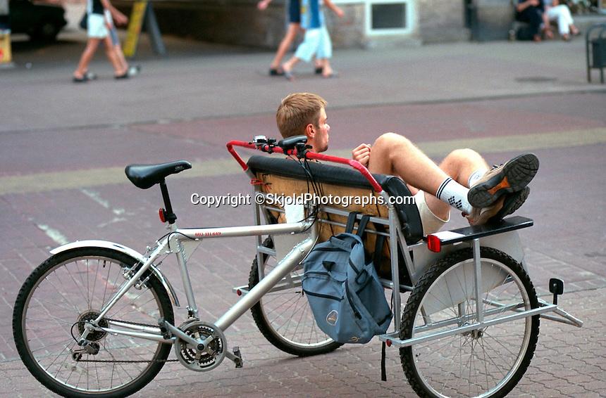 Bicycle taxi driver age 20 taking a break with feet up. Piotrkowska Street Lodz Poland