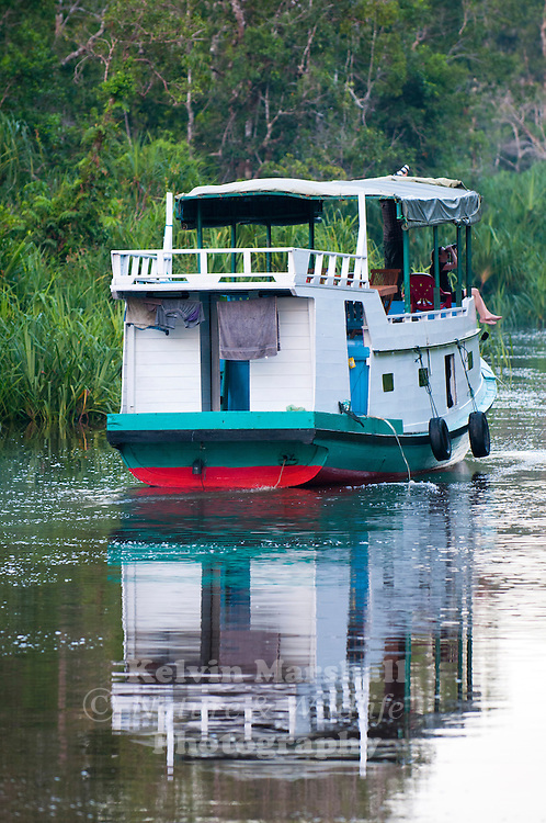 Tourists enjoying their live aboard experience on a traditional Klotok. A Klotok is a river boat used to navigate the waters of Indonesia. Tanjung Puting National Park, - Central Kalimantan, Indonesia.
