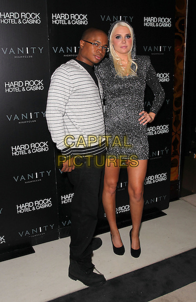 SAM JONES III & KARISSA SHANNON.Karissa and Kristina Shannon celebrate their 21st birthday at Vanity Nightclub inside the Hard Rock Hotel and Casino, Las Vegas, Nevada, USA, .2nd October 2010..full length dress hand on hip grey gray hood hooded sparkly shoes platform heels black Couple striped jumper top sweater glasses white .CAP/ADM/MJT.© MJT/AdMedia/Capital Pictures.
