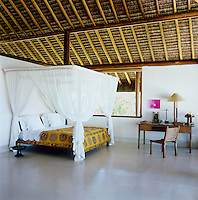 The four-poster bed in the master bedroom is made from eucalyptus trunks, the mosquito net is Balinese and the bedcover is an antique suzani