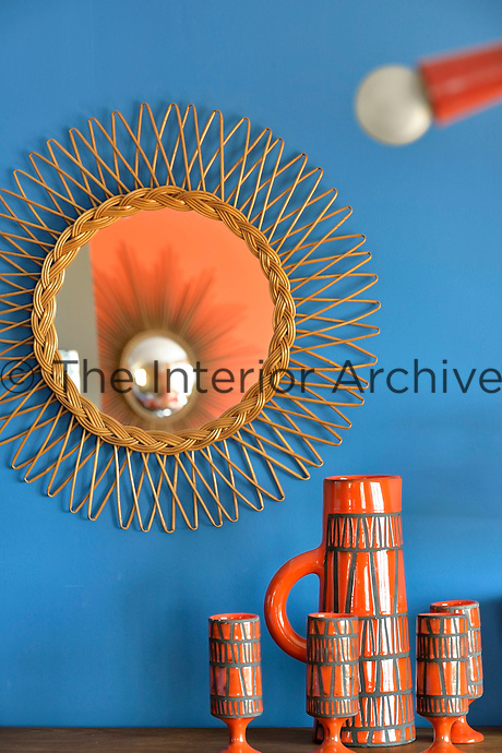 An ornamental mirror above a collection of ceramics in the living room